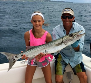Small girl catches large barracuda.